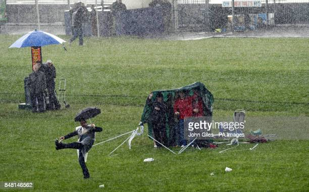 A short rain storm sweeps across the Knavesmire blowing this tent away as Racegoers try to keep dry on Mid Summer Raceday during the June Meeting at...