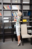 short senior woman stretches on tiptoe for documents in office