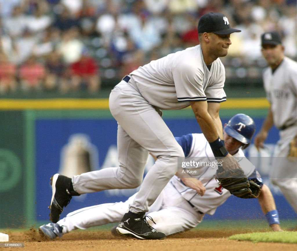 Short stop Michael Young of the Texas Rangers beats the throw from catcher Jorge Posada of the New York Yankees and slides in safely under short stop...