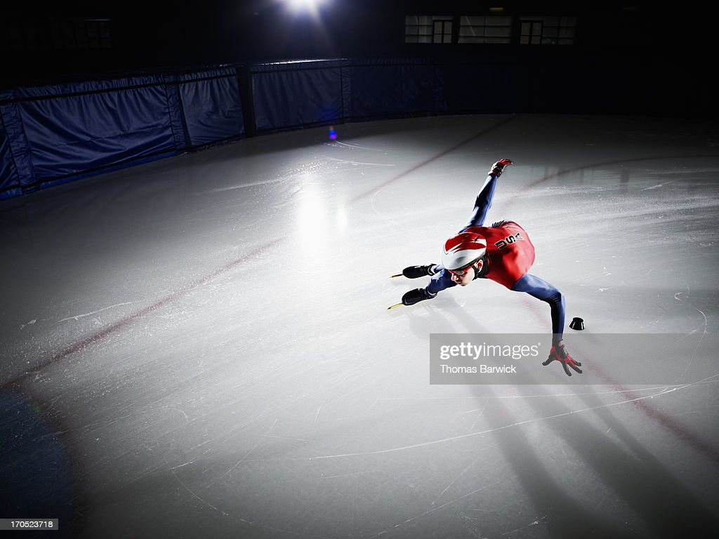 Short track speed skater making turn during race