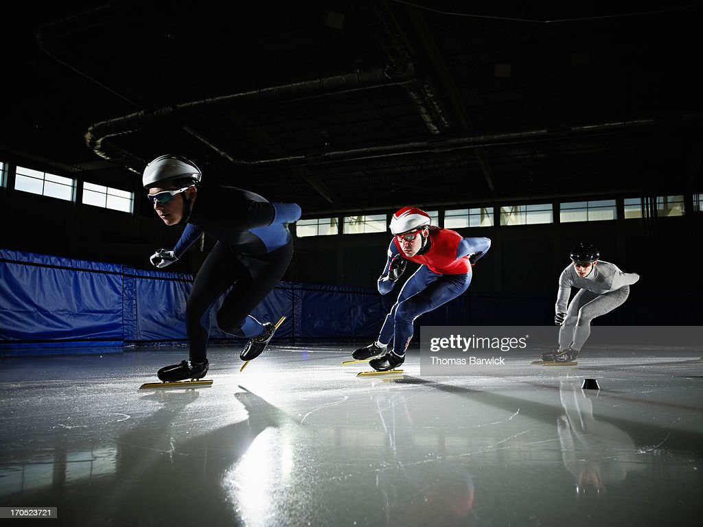 Short track speed skaters in turn during race : Stock Photo