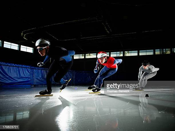 Short track speed skaters in turn during race
