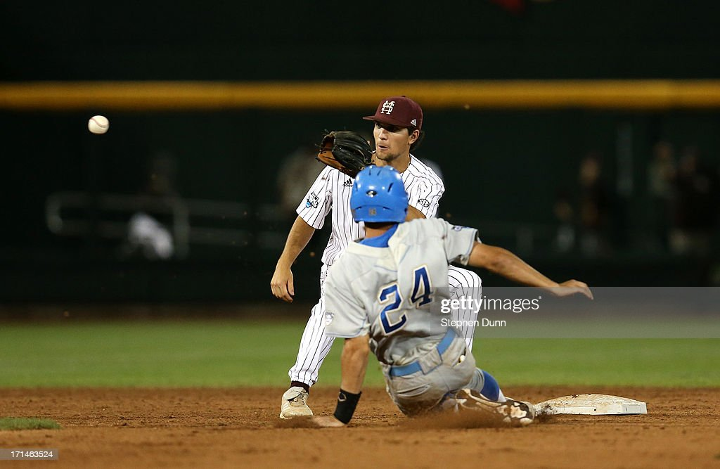 Shortstop Adam Frazier #12 of the Mississippi State Bulldogs takes the throw before tagging out Brian Carroll #24 of the UCLA Bruins attempting to steal second during game one of the College World Series Finals on June 24, 2013 at TD Ameritrade Park in Omaha, Nebraska. UCLA won 3-1.