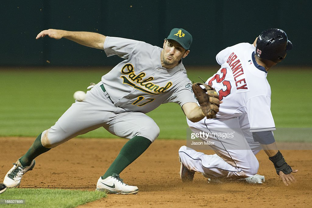 Shortstop <a gi-track='captionPersonalityLinkClicked' href=/galleries/search?phrase=Adam+Rosales&family=editorial&specificpeople=4921731 ng-click='$event.stopPropagation()'>Adam Rosales</a> #17 of the Oakland Athletics tries to catch as wild throw as Michael Brantley #23 of the Cleveland Indians steal second during the seventh inning at Progressive Field on May 8, 2013 in Cleveland, Ohio.