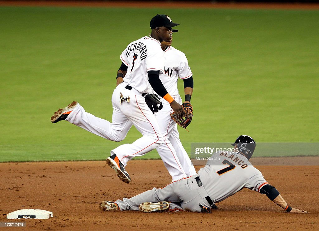 Shortstop <a gi-track='captionPersonalityLinkClicked' href=/galleries/search?phrase=Adeiny+Hechavarria&family=editorial&specificpeople=6926508 ng-click='$event.stopPropagation()'>Adeiny Hechavarria</a> #3 of the Miami Marlins turns a double play against <a gi-track='captionPersonalityLinkClicked' href=/galleries/search?phrase=Gregor+Blanco&family=editorial&specificpeople=4137600 ng-click='$event.stopPropagation()'>Gregor Blanco</a> #7 of the San Francisco Giants at Marlins Park on August 17, 2013 in Miami, Florida. The Giants defeated the Marlins 6-4.