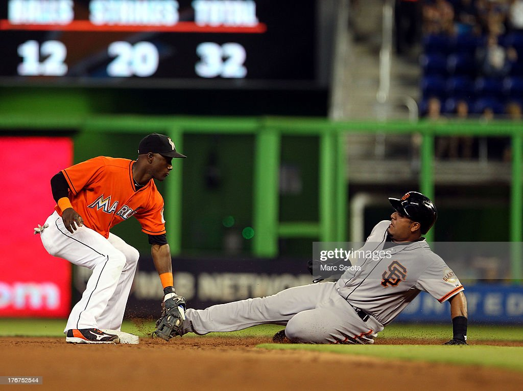 Shortstop <a gi-track='captionPersonalityLinkClicked' href=/galleries/search?phrase=Adeiny+Hechavarria&family=editorial&specificpeople=6926508 ng-click='$event.stopPropagation()'>Adeiny Hechavarria</a> #3 of the Miami Marlins turns a double play against Hector Sanchez #29 of the San Francisco Giants at Marlins Park on August 18, 2013 in Miami, Florida.