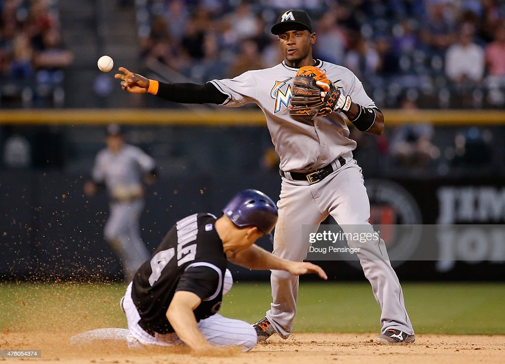 Shortstop Adeiny Hechavarria #3 of the Miami Marlins turns a double play on Nick Hundley #4 of the Colorado Rockies on a ground ball by Brandon Barnes #1 of the Colorado Rockies to end the fifth inning at Coors Field on June 5, 2015 in Denver, Colorado.