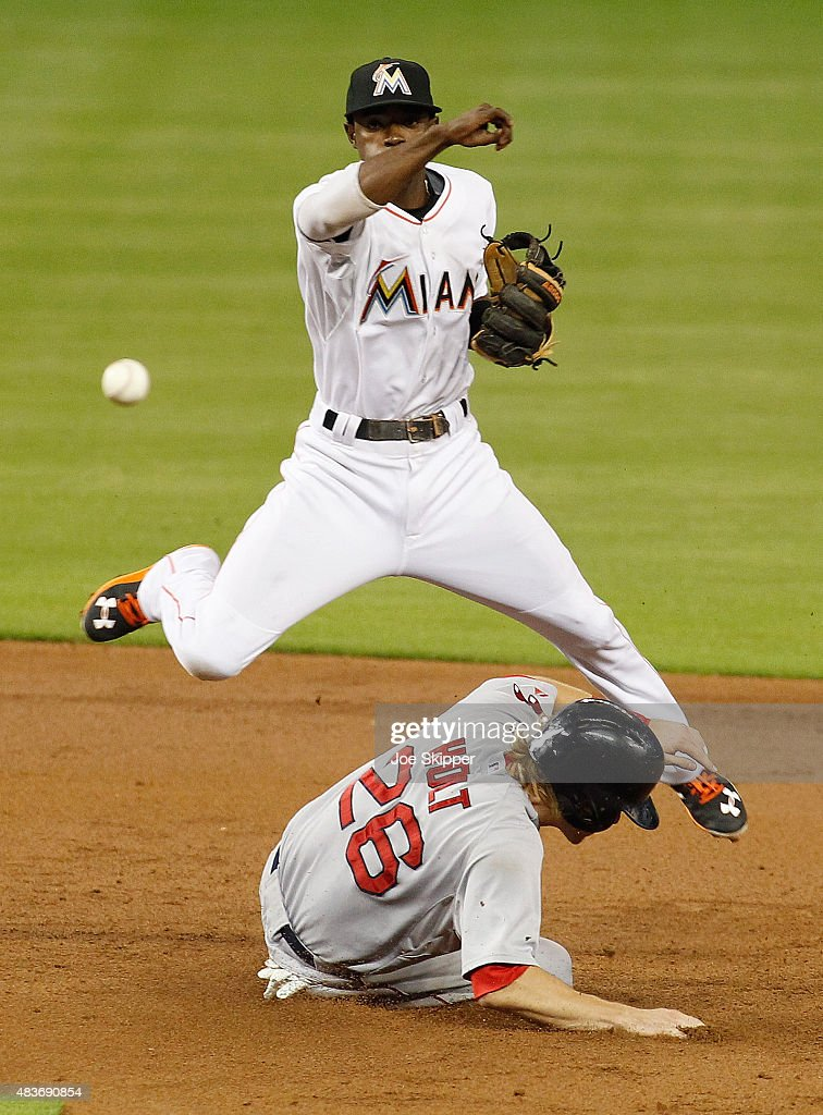 Shortstop Adeiny Hechavarria #3 of the Miami Marlins turns a double play in the third inning with Brock Holt #26 of the Boston Red Sox out at second base at Marlins Park on August 11, 2015 in Miami, Florida.