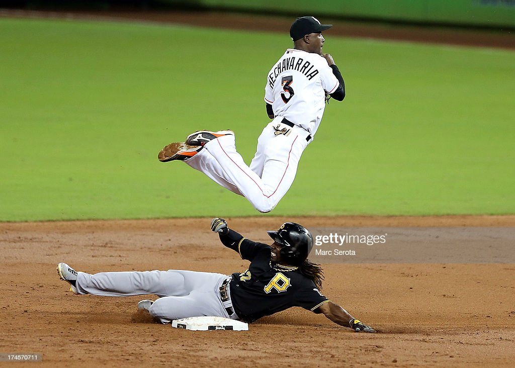 Shortstop Adeiny Hechevarria #4 of the Miami Marlins trys to turn a double play against Andrew McCutchin #22 of the Pittsburgh Pirates during the third inning at Marlins Park on July 27, 2013 in Miami, Florida.