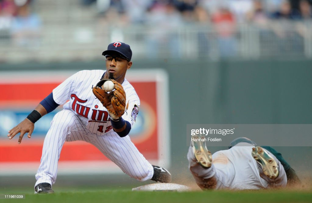 Shortstop <a gi-track='captionPersonalityLinkClicked' href=/galleries/search?phrase=Alexi+Casilla&family=editorial&specificpeople=4180372 ng-click='$event.stopPropagation()'>Alexi Casilla</a> #12 of the Minnesota Twins catches <a gi-track='captionPersonalityLinkClicked' href=/galleries/search?phrase=David+DeJesus&family=editorial&specificpeople=206765 ng-click='$event.stopPropagation()'>David DeJesus</a> #12 of the Oakland Athletics stealing during the ninth inning of their game on April 10, 2011 at Target Field in Minneapolis, Minnesota. Athletics defeated the Twins 5-3.