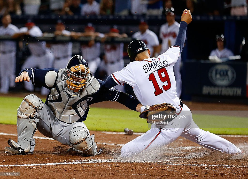 Shortstop <a gi-track='captionPersonalityLinkClicked' href=/galleries/search?phrase=Andrelton+Simmons&family=editorial&specificpeople=8978424 ng-click='$event.stopPropagation()'>Andrelton Simmons</a> #19 of the Atlanta Braves slides behind catcher <a gi-track='captionPersonalityLinkClicked' href=/galleries/search?phrase=Derek+Norris&family=editorial&specificpeople=6795804 ng-click='$event.stopPropagation()'>Derek Norris</a> #3 of the San Diego Padres in the sixth inning to score the tying run during the game at Turner Field on June 9, 2015 in Atlanta, Georgia.