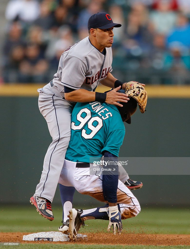 Shortstop Asdrubal Cabrera of the Cleveland Indians bumps into James Jones of the Seattle Mariners after throwing to first on a double play in the...