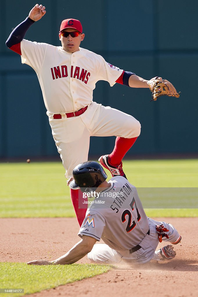 Shortstop <a gi-track='captionPersonalityLinkClicked' href=/galleries/search?phrase=Asdrubal+Cabrera&family=editorial&specificpeople=834042 ng-click='$event.stopPropagation()'>Asdrubal Cabrera</a> #13 of the Cleveland Indians jumps over <a gi-track='captionPersonalityLinkClicked' href=/galleries/search?phrase=Giancarlo+Stanton&family=editorial&specificpeople=8983978 ng-click='$event.stopPropagation()'>Giancarlo Stanton</a> #27 of the Miami Marlins after turning the double play during the seventh inning at Progressive Field on May 19, 2012 in Cleveland, Ohio.