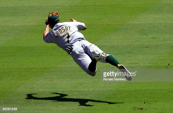 Shortstop Bobby Crosby of the Oakland Athletics makes a diving catch against Sandy Alomar Jr #15 of the Texas Rangers on July 24 2005 at Ameriquest...