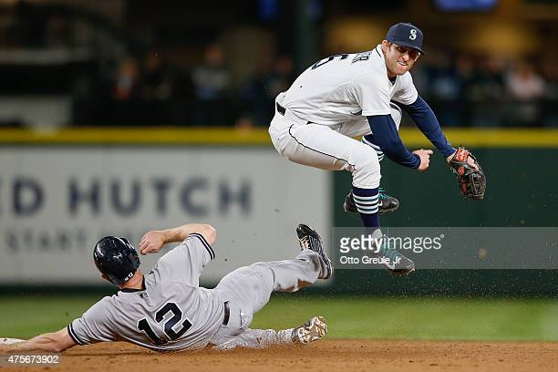 Shortstop Brad Miller of the Seattle Mariners turns a double play over Chase Headley of the New York Yankees to end the top of the tenth inning at...