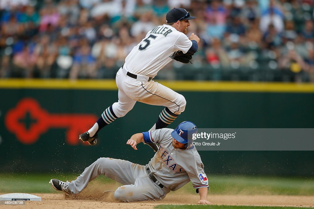 Shortstop Brad Miller #5 of the Seattle Mariners turns a double play over Ryan Strausborger #20 of the Texas Rangers in the tenth inning at Safeco Field on August 8, 2015 in Seattle, Washington.
