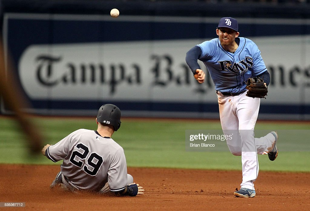 Shortstop <a gi-track='captionPersonalityLinkClicked' href=/galleries/search?phrase=Brad+Miller+-+Baseball+Player&family=editorial&specificpeople=14752161 ng-click='$event.stopPropagation()'>Brad Miller</a> #13 of the Tampa Bay Rays gets the out on <a gi-track='captionPersonalityLinkClicked' href=/galleries/search?phrase=Dustin+Ackley&family=editorial&specificpeople=4352278 ng-click='$event.stopPropagation()'>Dustin Ackley</a> #29 of the New York Yankees at second base then turns the double play for the out on Ronald Torreyes at first base to end the top of the sixth inning of a game on May 29, 2016 at Tropicana Field in St. Petersburg, Florida.