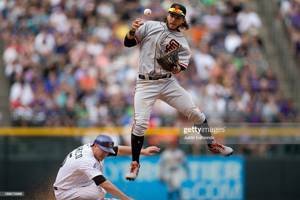Shortstop <a gi-track='captionPersonalityLinkClicked' href=/galleries/search?phrase=Brandon+Crawford&family=editorial&specificpeople=5580312 ng-click='$event.stopPropagation()'>Brandon Crawford</a> #35 of the San Francisco Giants bobbles the exchange while jumping over <a gi-track='captionPersonalityLinkClicked' href=/galleries/search?phrase=Jordan+Pacheco&family=editorial&specificpeople=6889136 ng-click='$event.stopPropagation()'>Jordan Pacheco</a> #15 of the Colorado Rockies allowing the runner at first base to be safe during the fifth inning at Coors Field on May 19, 2013 in Denver, Colorado. The Rockies defeated the Giants 5-0.