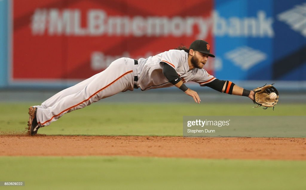 Shortstop Brandon Crawford #35 of the San Francisco Giants dives to get a ground ball hit by Kike Hernandez #14 of the Los Angeles Dodgers for the final out of the second inning at Dodger Stadium on September 23, 2017 in Los Angeles, California.