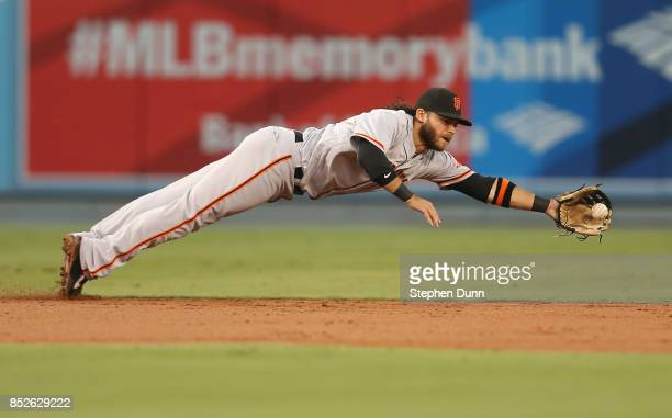 Shortstop Brandon Crawford of the San Francisco Giants dives to get a ground ball hit by Kike Hernandez of the Los Angeles Dodgers for the final out...