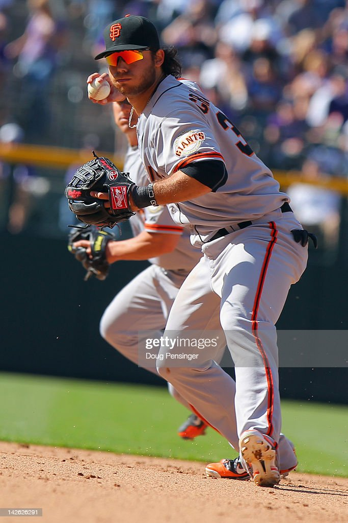 Shortstop <a gi-track='captionPersonalityLinkClicked' href=/galleries/search?phrase=Brandon+Crawford&family=editorial&specificpeople=5580312 ng-click='$event.stopPropagation()'>Brandon Crawford</a> #35 of the San Francisco Giants fields the ball and throws out as runner against the Colorado Rockies as second baseman Ryan Theriot #5 of the San Francisco Giants backs up the play on Opening Day at Coors Field on April 9, 2012 in Denver, Colorado. The Giants defeated the Rockies 7-0.