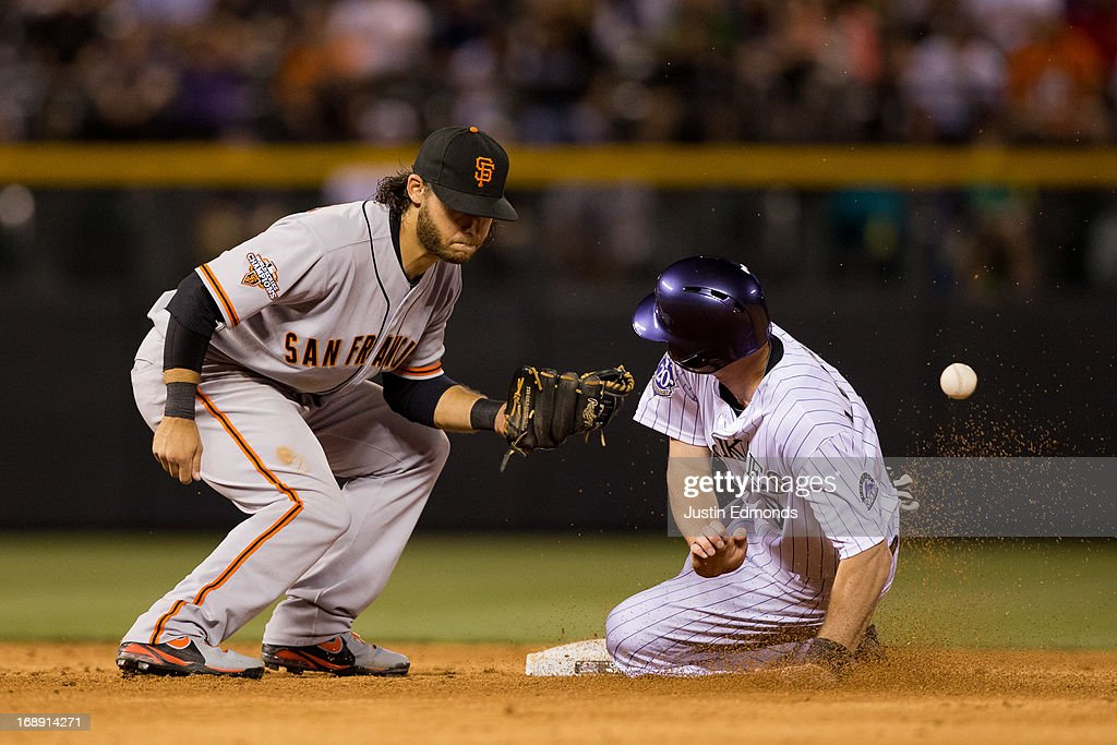 Shortstop <a gi-track='captionPersonalityLinkClicked' href=/galleries/search?phrase=Brandon+Crawford&family=editorial&specificpeople=5580312 ng-click='$event.stopPropagation()'>Brandon Crawford</a> #35 of the San Francisco Giants is unable to control the throw as D.J. LeMahieu #9 of the Colorado Rockies slides in safely with a stolen base during the sixth inning at Coors Field on May 16, 2013 in Denver, Colorado. The Giants defeated the Rockies 8-6.