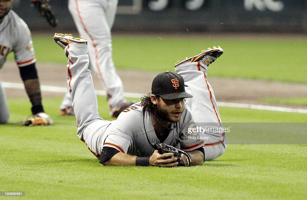 Shortstop Brandon Crawford #35 of the San Francisco Giants makes a diving catch after third baseman Pablo Sandoval #48 of the San Francisco Giants had the ball pop out of his glove against the Houston Astros at Minute Maid Park on August 28, 2012 in Houston, Texas.