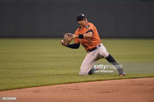 Shortstop Carlos Correa of the Houston Astros throws to first base from his knees after diving to catch a ground ball in the game against the Kansas...