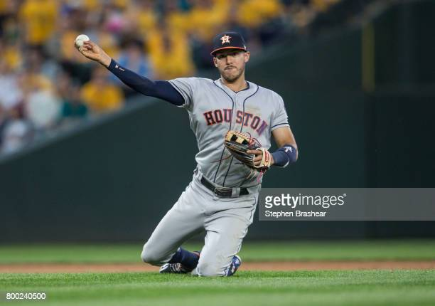 Shortstop Carlos Correa of the Houston Astros throws to first base after diving to field a a ball hit by Ben Gamel of the Seattle Mariners during the...