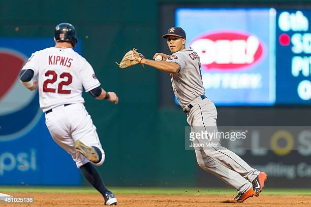 Shortstop Carlos Correa of the Houston Astros throws to first for a double play while Jason Kipnis of the Cleveland Indians is out at second during...