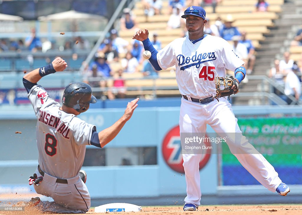 Shortstop Carlos Triunfel #45 of the Los Angeles Dodgers loses control of the ball after transfering it to his throwing hand after forcing out <a gi-track='captionPersonalityLinkClicked' href=/galleries/search?phrase=Lonnie+Chisenhall&family=editorial&specificpeople=6796448 ng-click='$event.stopPropagation()'>Lonnie Chisenhall</a> #8 of the Cleveland Indians at Dodger Stadium on July 2, 2014 in Los Angeles, California. The Indians won 5-4.