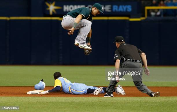 Shortstop Chad Pinder of the Oakland Athletics leaps over Mallex Smith of the Tampa Bay Rays as Smith steals second base during the fifth inning of...