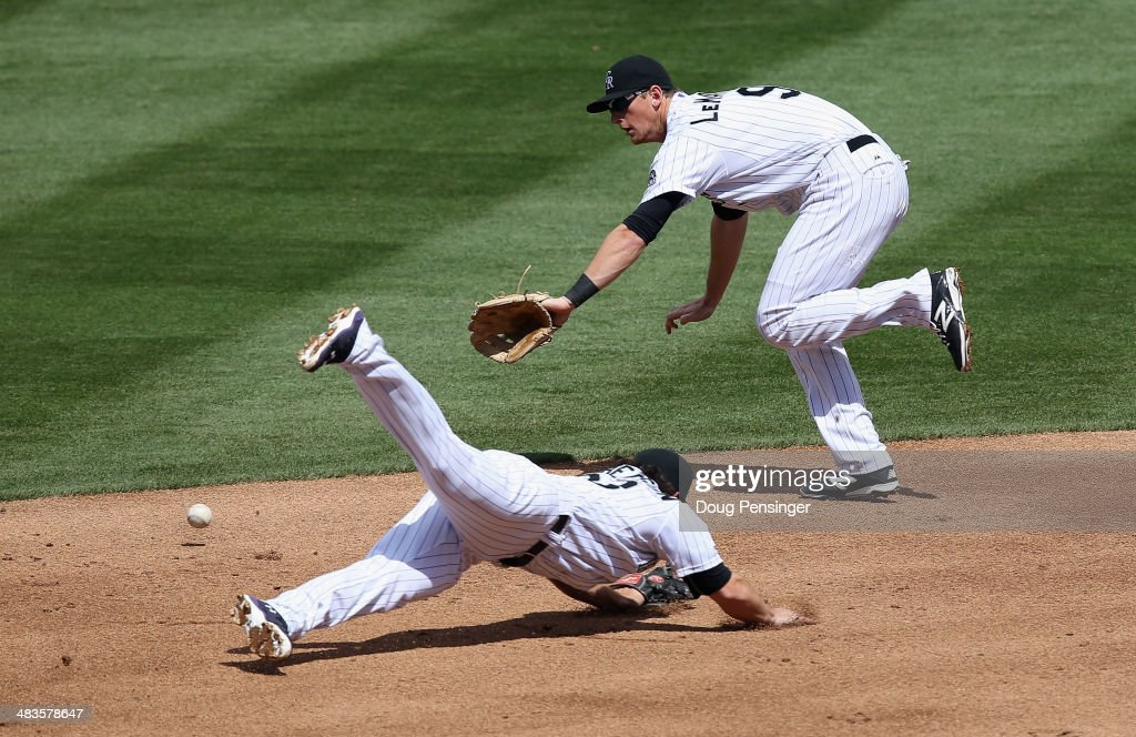 Shortstop Charlie Culberson #23 of the Colorado Rockies and second baseman <a gi-track='captionPersonalityLinkClicked' href=/galleries/search?phrase=DJ+LeMahieu&family=editorial&specificpeople=5940806 ng-click='$event.stopPropagation()'>DJ LeMahieu</a> #9 of the Colorado Rockies can't stop a ground ball by Alexei Ramirez #10 of the Chicago White Sox in the second inning during Interleague play at Coors Field on April 9, 2014 in Denver, Colorado.