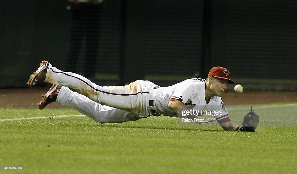 Shortstop Chris Owings #16 of the Arizona Diamondbacks has the ball bounce away after trying to make a diving catch of a shallow fly ball against the San Francisco Giants during the ninth inning of a MLB game at Chase Field on April 1, 2014 in Phoenix, Arizona.