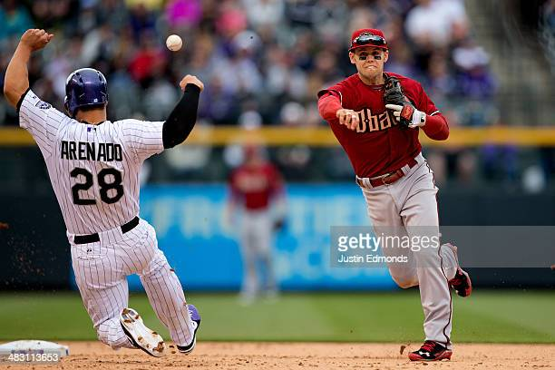 Shortstop Chris Owings of the Arizona Diamondbacks throws to first base to complete the double play and end the fifth inning as Nolan Arenado of the...