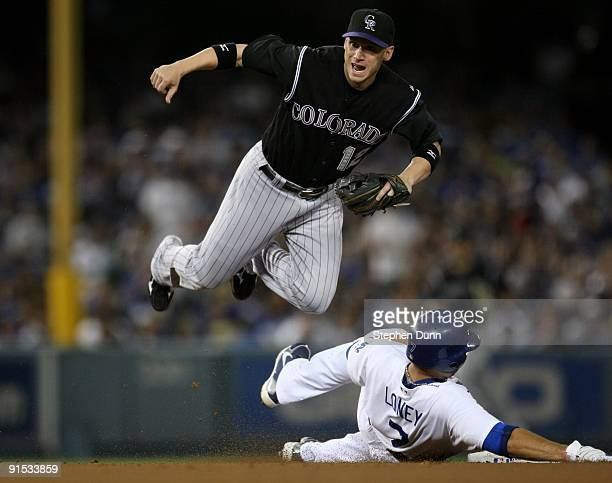Shortstop Clint Barmes of the Colorado Rockies watches his throw to first to turn the double play as he jumps over James Loney of the Los Angeles...