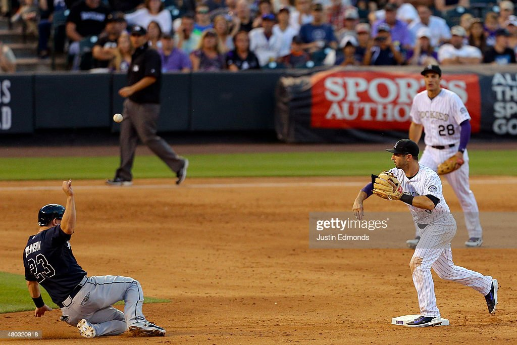 Shortstop Daniel Descalso of the Colorado Rockies throws to first base to complete the double play to end the sixth inning as Nolan Arenado looks on...