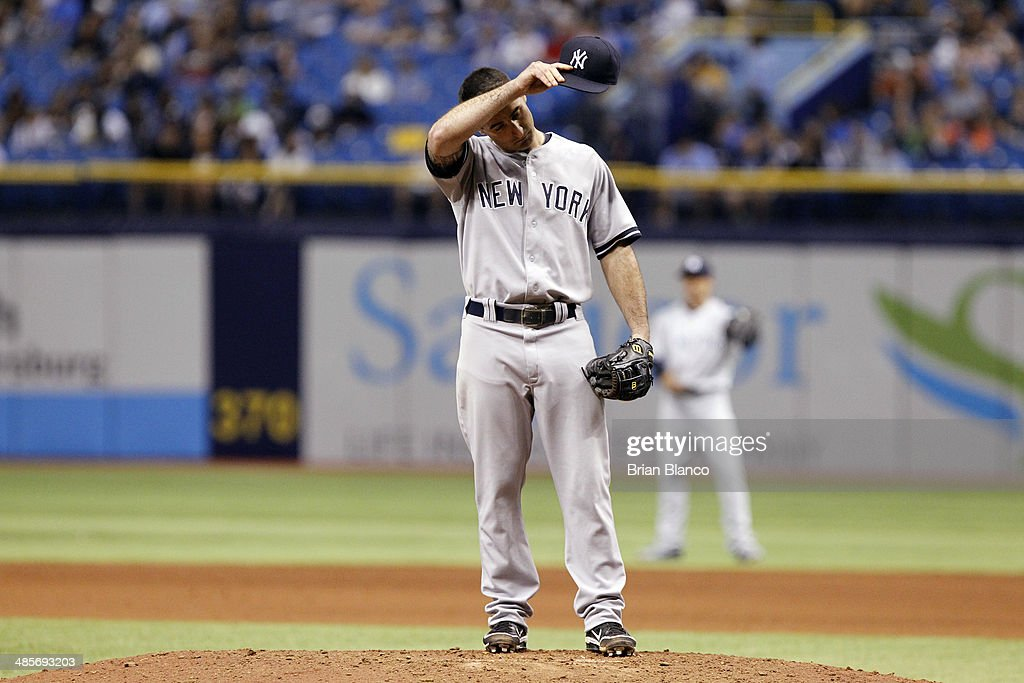 Shortstop Dean Anna #45 of the New York Yankees wipes his brow as he steps to the mound to take over pitching duties during the eighth inning of a game against the Tampa Bay Rays on April 19, 2014 at Tropicana Field in St. Petersburg, Florida.