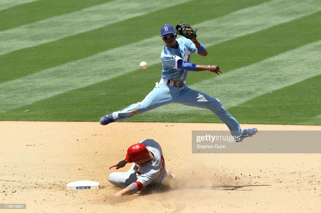 Shortstop Dee Gordon the Los Angeles Dodgers throws to first but can't turn the double play after forcing out Joey Votto of the Cincinnati Reds in...