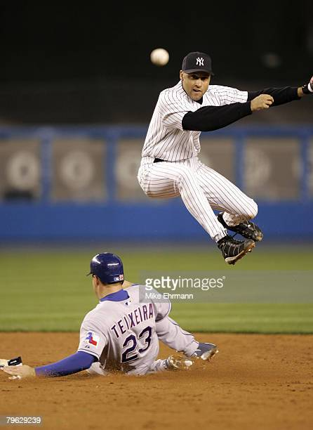 Shortstop Derek Jeter of the New York Yankees jumps over Texas Ranger Mark Texeira on a double play at Yankee Stadium in the Bronx New York on April...