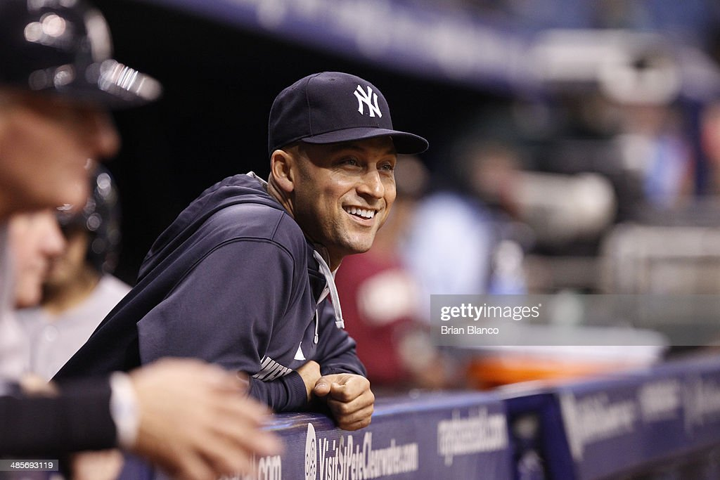 Shortstop Derek Jeter of the New York Yankees laughs from the dugout as fellow shortstop Dean Anna of the New York Yankees takes over pitching duties during the eighth inning of a game against the Tampa Bay Rays on April 19, 2014 at Tropicana Field in St. Petersburg, Florida.