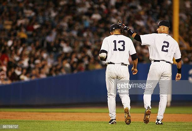 Shortstop Derek Jeter of the New York Yankees pats third baseman Alex Rodriguez on the head after Rodriguez made a play to first base for an out in...