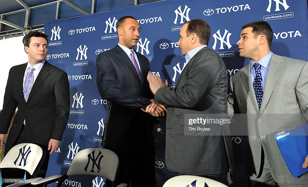 Shortstop Derek Jeter of the New York Yankees shakes hands with General Manager Brian Cashman during a press conference to announce his new contract...