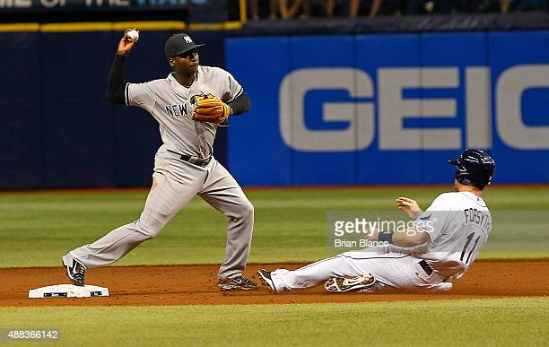 Shortstop Didi Gregorius of the New York Yankees turns a double play over Logan Forsythe of the Tampa Bay Rays to end the first inning of a game on...