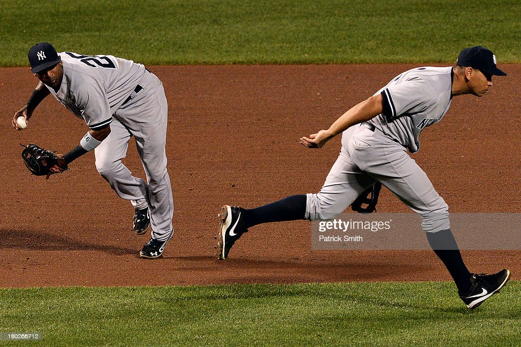 Shortstop <a gi-track='captionPersonalityLinkClicked' href=/galleries/search?phrase=Eduardo+Nunez&family=editorial&specificpeople=4900197 ng-click='$event.stopPropagation()'>Eduardo Nunez</a> #26 of the New York Yankees looks to make a play against the Baltimore Orioles as teammate third baseman Alex Rodriguez #13 ducks out of the way in the fifth inning at Oriole Park at Camden Yards on September 10, 2013 in Baltimore, Maryland.