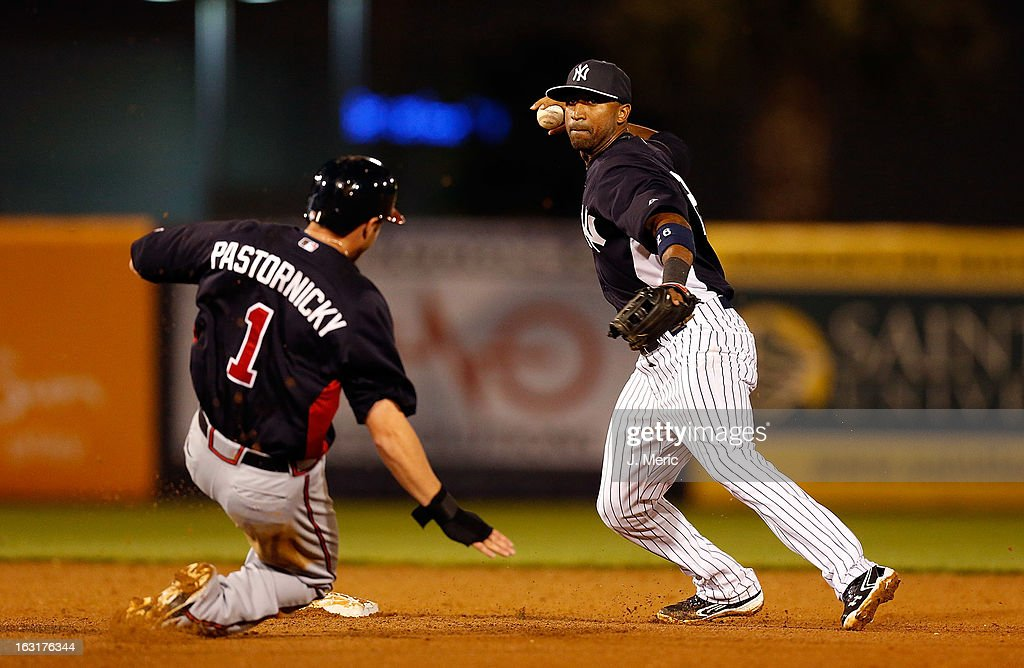 Shortstop Eduardo Nunez #26 of the New York Yankees turns a double play as infielder Tyler Pastornicky #1 of the Atlanta Braves tries to break it up during a Grapefruit League Spring Training Game at George M. Steinbrenner Field on March 5, 2013 in Tampa, Florida.