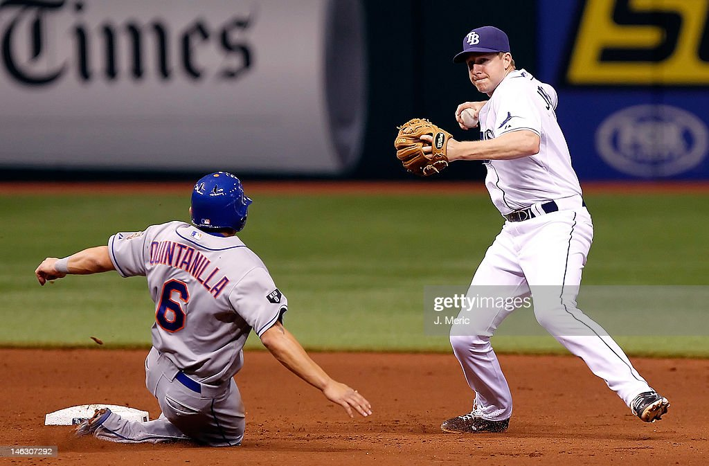 Shortstop <a gi-track='captionPersonalityLinkClicked' href=/galleries/search?phrase=Elliot+Johnson+-+Baseball+Player&family=editorial&specificpeople=4175454 ng-click='$event.stopPropagation()'>Elliot Johnson</a> #9 of the Tampa Bay Rays turns a double play as Omar Quintanilla #6 of the New York Mets tries to break it up during the game at Tropicana Field on June 13, 2012 in St. Petersburg, Florida.