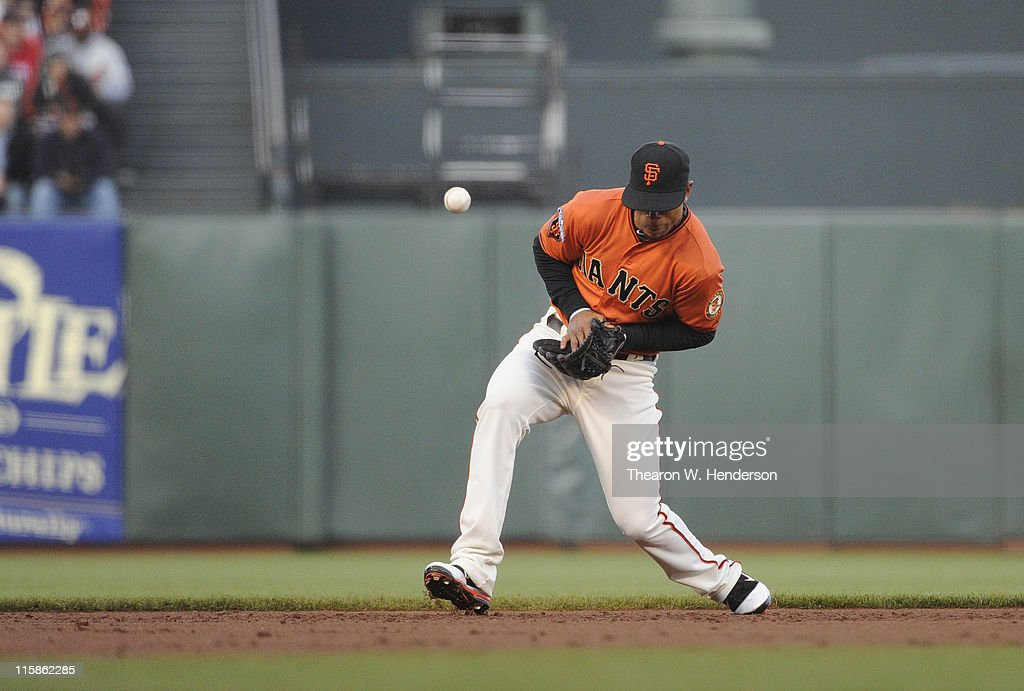 Shortstop Emmanuel Burriss #2 of the San Francisco Giants has the ball kick off the back of his glove for an error during a MLB baseball game against the Cincinnati Reds June 10, 2011 at AT&T Park in San Francisco, California.