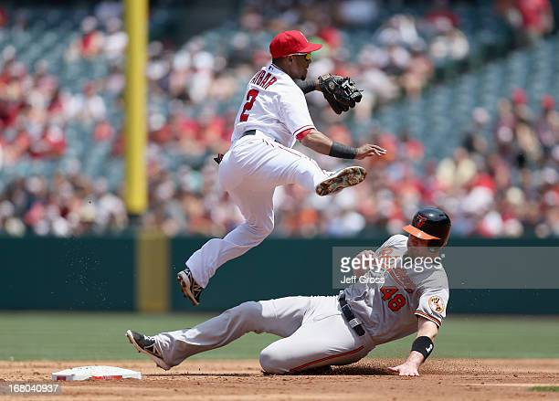 Shortstop Erick Aybar of the Los Angeles Angels of Anaheim forces Chris Snyder of the Baltimore Orioles out at second base before throwing to first...