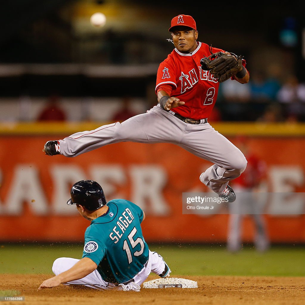 Shortstop <a gi-track='captionPersonalityLinkClicked' href=/galleries/search?phrase=Erick+Aybar&family=editorial&specificpeople=551376 ng-click='$event.stopPropagation()'>Erick Aybar</a> #2 of the Los Angeles Angels of Anaheim turns a double play over <a gi-track='captionPersonalityLinkClicked' href=/galleries/search?phrase=Kyle+Seager&family=editorial&specificpeople=7682389 ng-click='$event.stopPropagation()'>Kyle Seager</a> #15 of the Seattle Mariners in the sixth inning at Safeco Field on August 23, 2013 in Seattle, Washington.